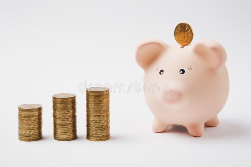 Moneda que cae en el banco guarro rosado del dinero, pilas de monedas de oro aisladas en el fondo blanco Acumulación del dinero imagenes de archivo