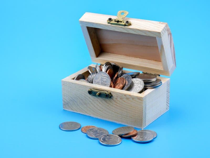 Moneda tailandesa en el pecho de madera en fondo azul imagen de archivo libre de regalías