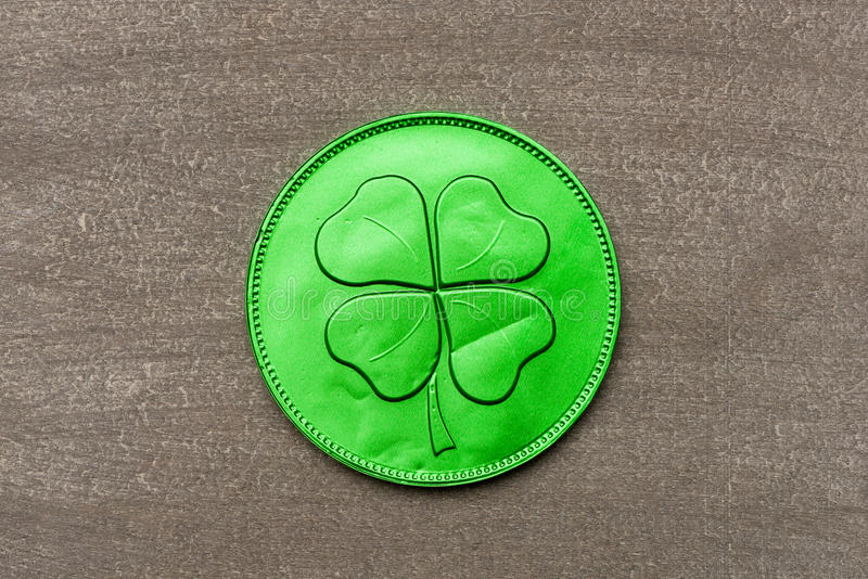 Moneda verde del chocolate con el trébol de cuatro hojas foto de archivo