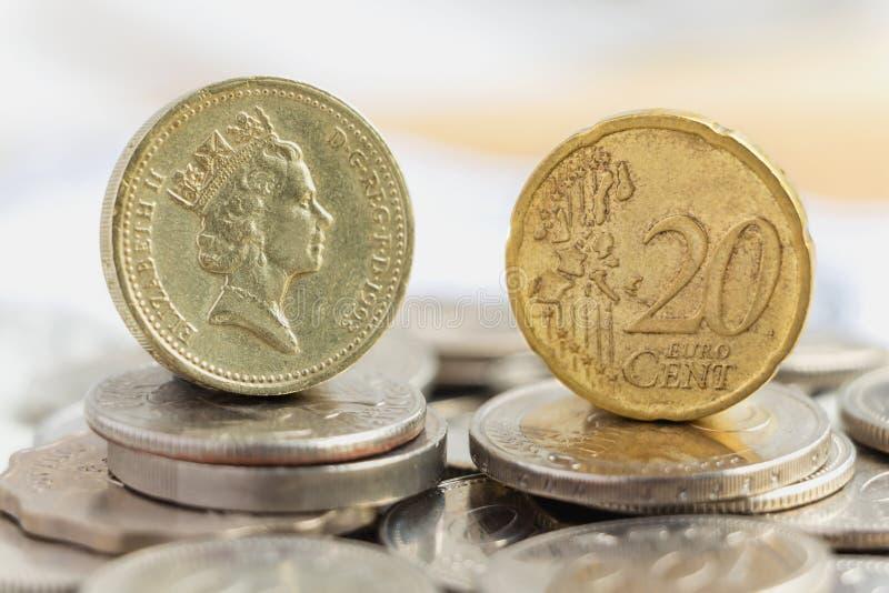 Moneda y británicos euro una moneda de libra en una pila de monedas La estafa fotografía de archivo libre de regalías