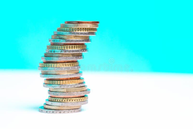 Monedas apiladas en uno a en diversas posiciones respecto a un fondo azul y blanco foto de archivo