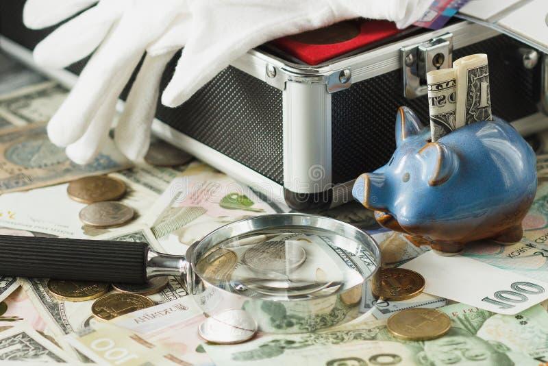 Monedas, billetes de banco con una lupa y hucha foto de archivo libre de regalías