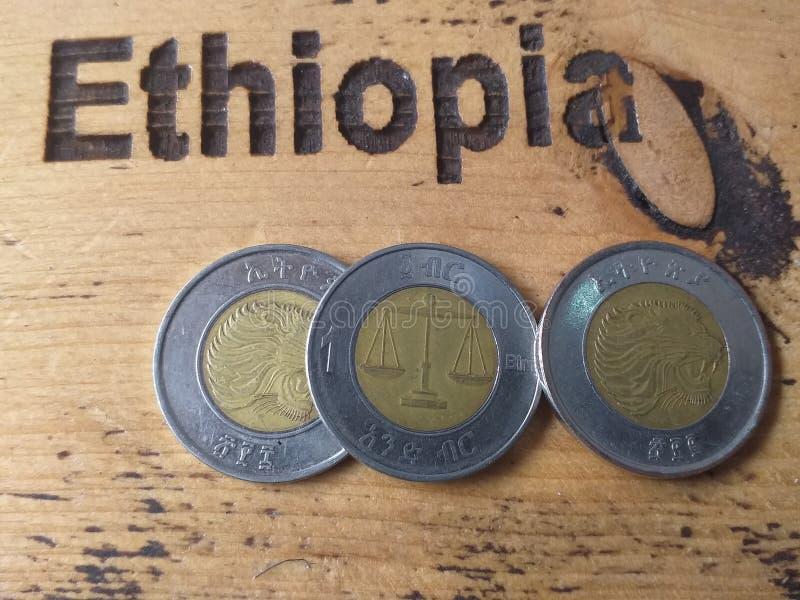 Monedas bimetálicas - un número reciente de un birr de Etiopía sobre una mesa de madera en la que el nombre 'Etiopía' marca imagen de archivo