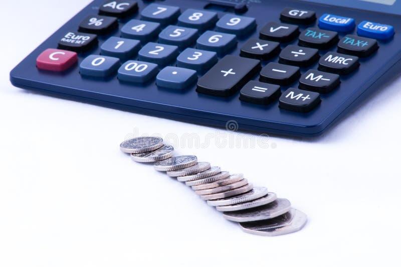 Monedas británicas y vista delantera dof de la calculadora imagenes de archivo