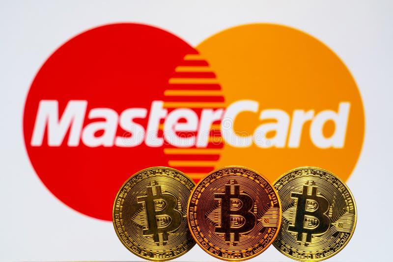 Monedas de Bitcoin del oro con el logotipo de Mastercard en fondo imagen de archivo libre de regalías
