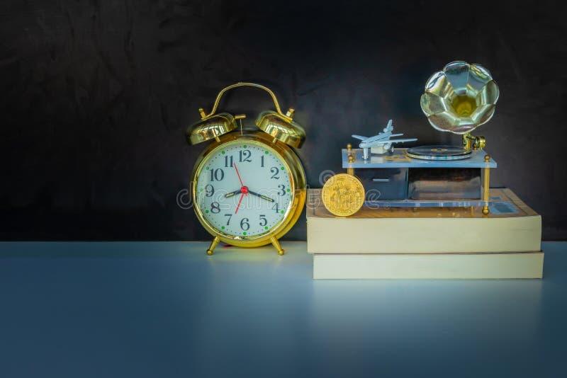 Monedas de Bitcoin en el oro viejo del despertador del libro, el modelo del avión de pasajeros y el fonógrafo sobre el fondo negr imagenes de archivo