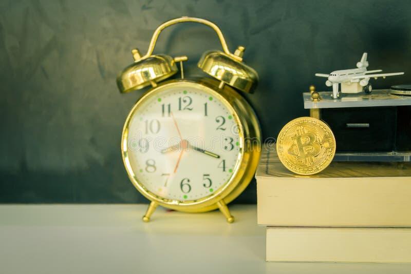 Monedas de Bitcoin en el oro viejo del despertador del libro, el modelo del avión de pasajeros y el fonógrafo sobre el fondo negr fotos de archivo