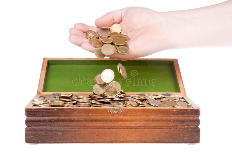 Monedas de caída de la mano en un pecho de tesoro imagenes de archivo