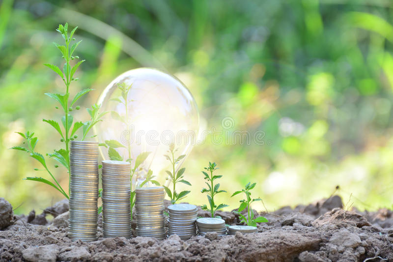 monedas de la bombilla y de la pila que sienten para el éxito o la energía solar o fotos de archivo libres de regalías