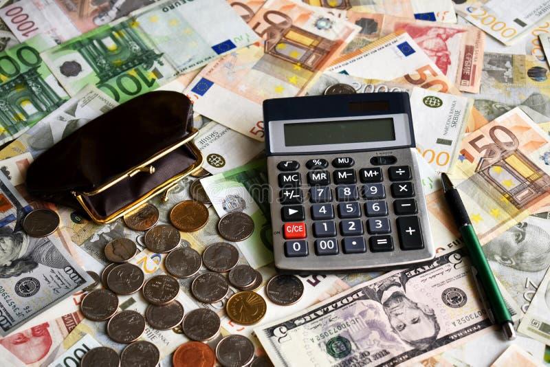 Monedas de la pluma de bola de la calculadora de la cartera y billetes fotografía de archivo libre de regalías