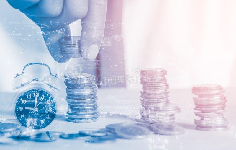 Monedas de las pilas del hombre de la exposición doble con el despertador y fondo de la ciudad de la noche, actividades bancarias foto de archivo libre de regalías