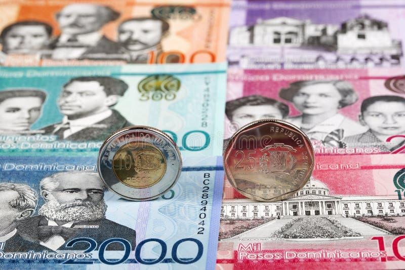 Monedas de los Pesos dominicanos en el fondo de billetes de banco imagenes de archivo
