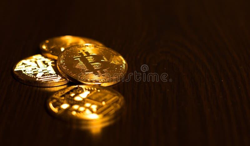 Monedas de oro de bitcoins en una tabla de la oficina en un fondo oscuro fotos de archivo