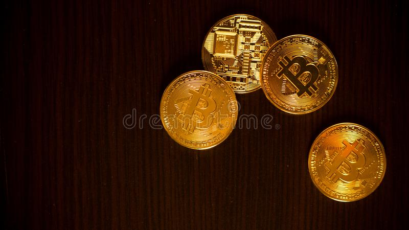 Monedas de oro de bitcoins en una tabla de la oficina en un fondo oscuro imagen de archivo libre de regalías