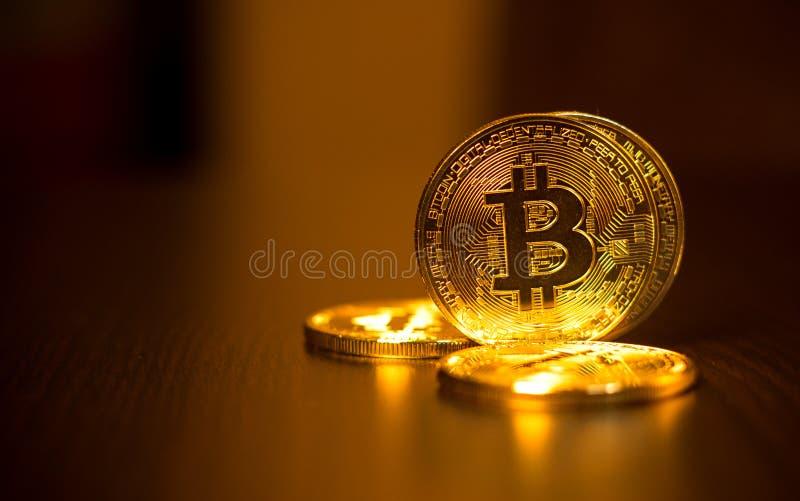 Monedas de oro de bitcoins en una tabla de la oficina en un fondo oscuro imagenes de archivo