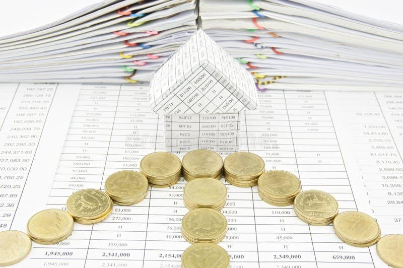Monedas de oro como flecha delante de la casa fotos de archivo