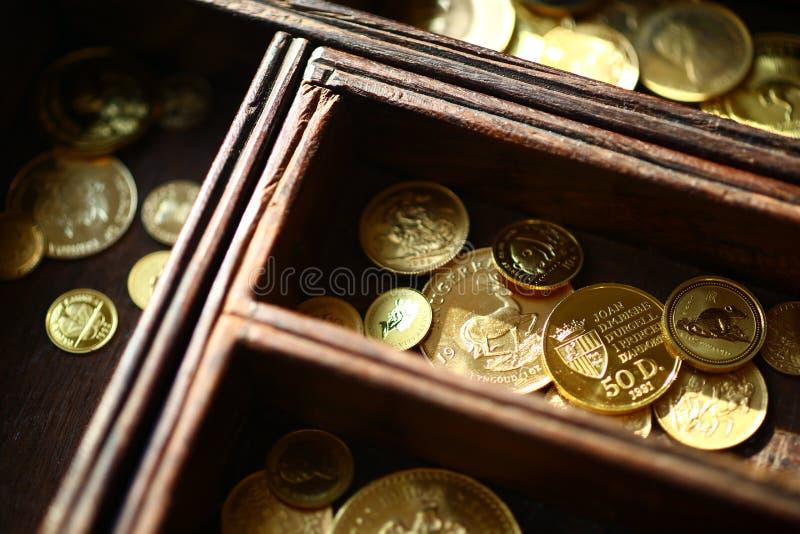 Monedas de oro en ataúd de madera foto de archivo