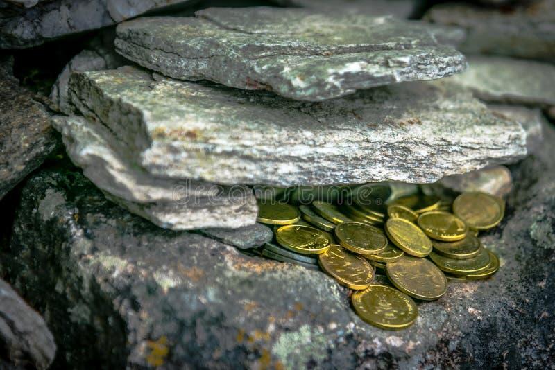 Monedas de oro en la roca fotografía de archivo libre de regalías