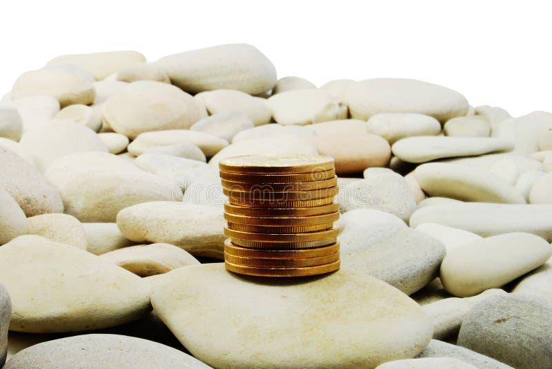 Monedas de oro en las piedras - aisladas imagen de archivo libre de regalías