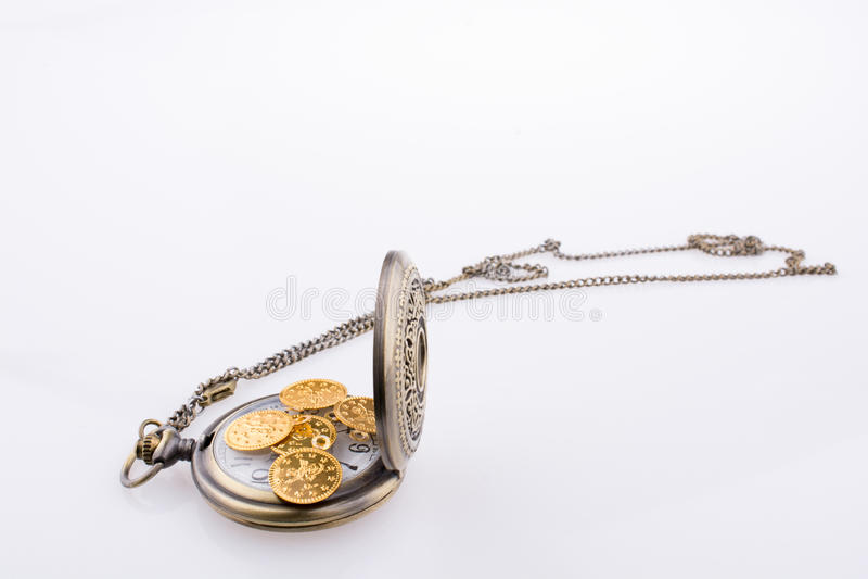 Monedas de oro falsas en un reloj de bolsillo fotos de archivo libres de regalías