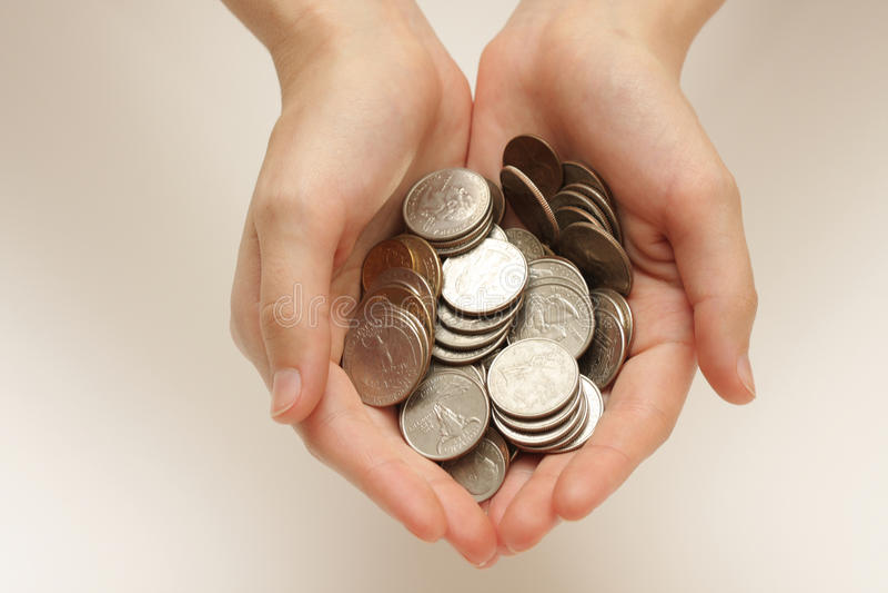 Monedas de plata en manos imagen de archivo