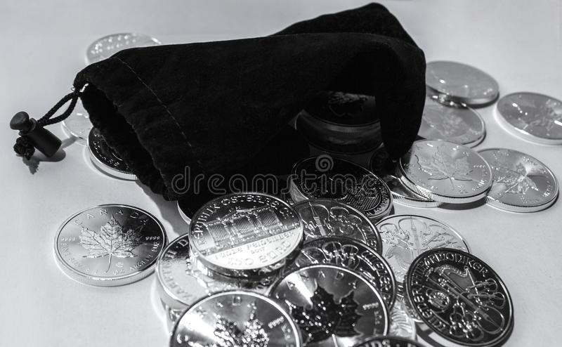 Monedas de plata de la inversión global con el monedero negro fotografía de archivo