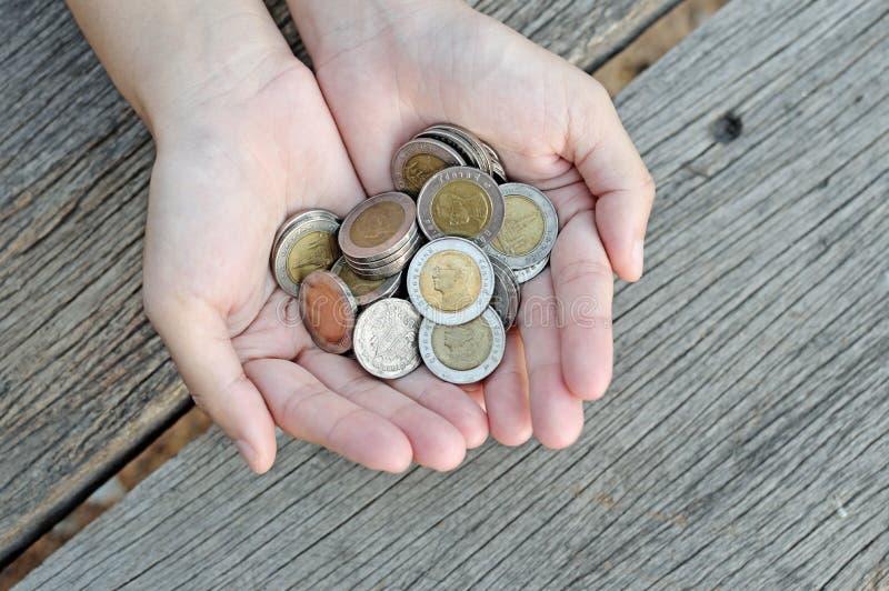 Monedas del control de las mujeres en la tabla de madera imagenes de archivo
