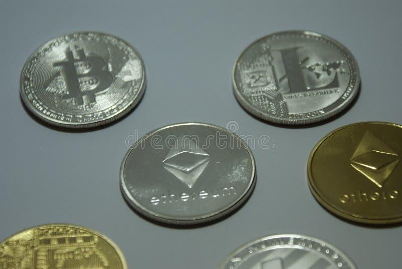 Monedas del cryptocurrency de la plata y del oro en un fondo blanco foto de archivo