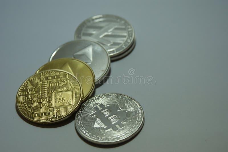 Monedas del cryptocurrency de la plata y del oro en un fondo blanco fotos de archivo
