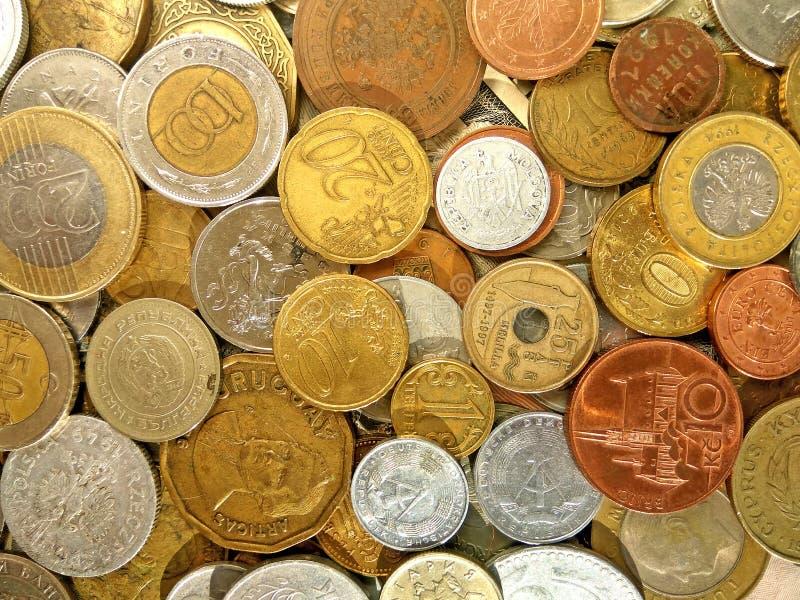 Monedas del dinero viejo de los países diferentes en fondo del dólar fotos de archivo libres de regalías