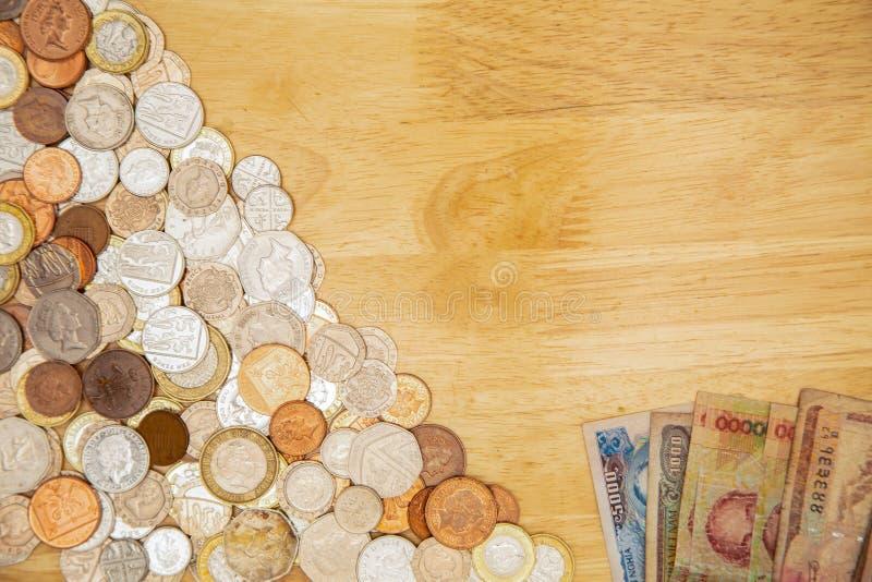 Monedas del Reino Unido con los billetes de banco extranjeros en una tabla fotografía de archivo