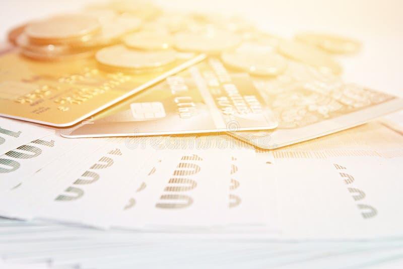 Monedas, dinero tailandés y tarjetas de crédito en el fondo blanco fotografía de archivo