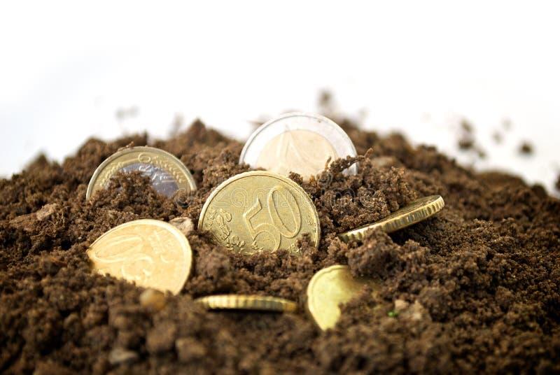 Monedas en concepto de la suciedad foto de archivo