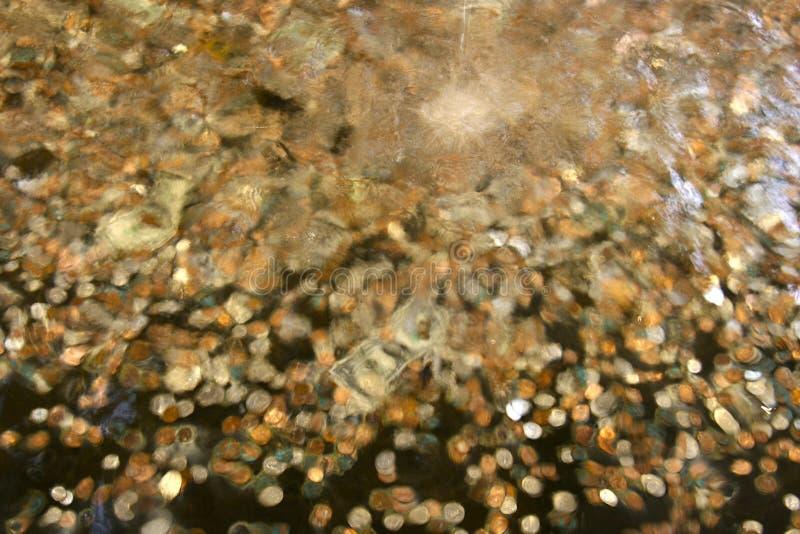 Monedas en la fuente fotos de archivo