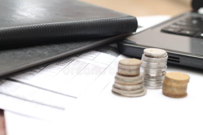 Monedas en la tabla, con los ordenadores portátiles y los informes financieros, versión 2 fotos de archivo