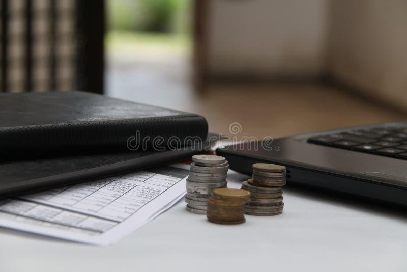 Monedas en la tabla, con los ordenadores portátiles y los informes financieros, versión 3 foto de archivo
