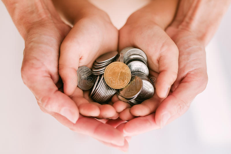 Monedas en las manos de la madre y del niño fotos de archivo