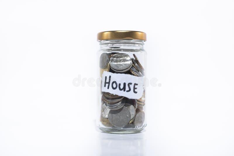 Monedas en un tarro con una nota escrita ` de la CASA del ` En un fondo blanco fotografía de archivo libre de regalías