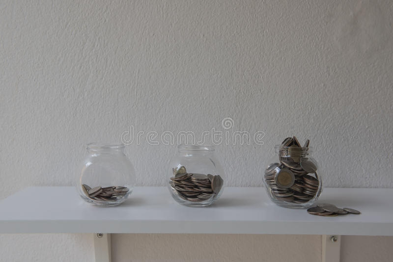 Monedas en un tarro de cristal, paso del dinero del ahorro del concepto con la moneda del depósito en negocio cada vez mayor de l fotografía de archivo