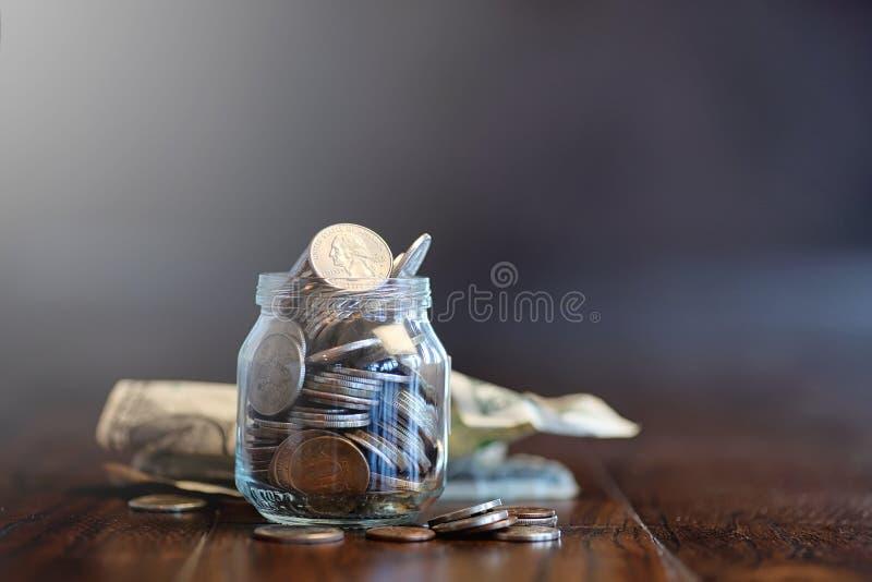 Monedas en un tarro de cristal en un piso de madera Ahorros del bolsillo de la moneda fotos de archivo libres de regalías