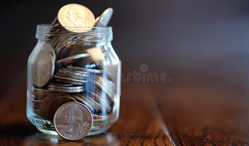 Monedas en un tarro de cristal en un piso de madera Ahorros del bolsillo de la moneda imagen de archivo libre de regalías