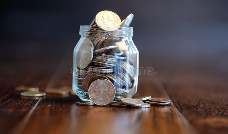 Monedas en un tarro de cristal en un piso de madera Ahorros del bolsillo de la moneda fotos de archivo