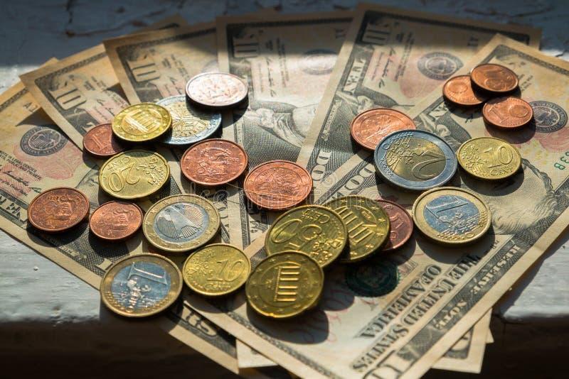 Monedas euro de diversas denominaciones en el fondo de billetes de dólar Primer de varias monedas euro Concepto de comercio en fotografía de archivo