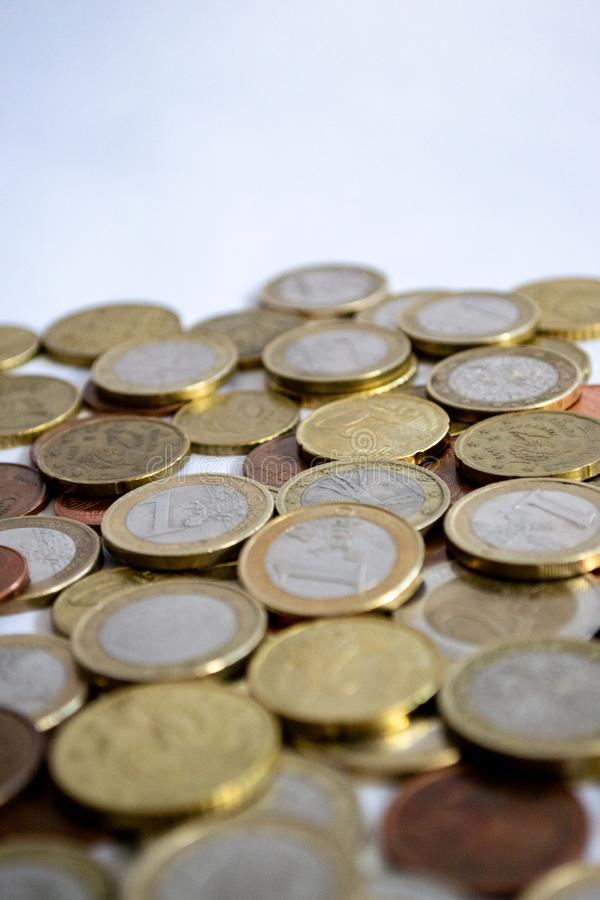 Monedas euro de la plata y del oro dispersados en un fondo blanco imagen de archivo libre de regalías