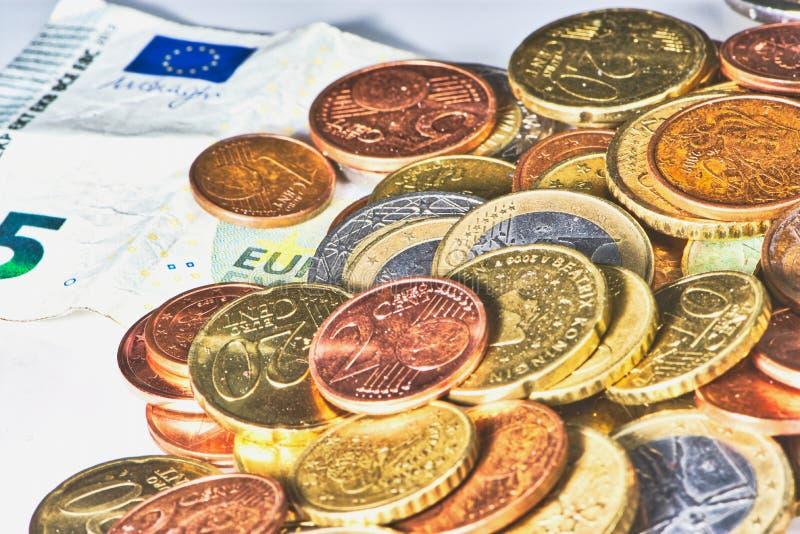 Monedas euro y centavos euro al lado de un billete de banco foto de archivo