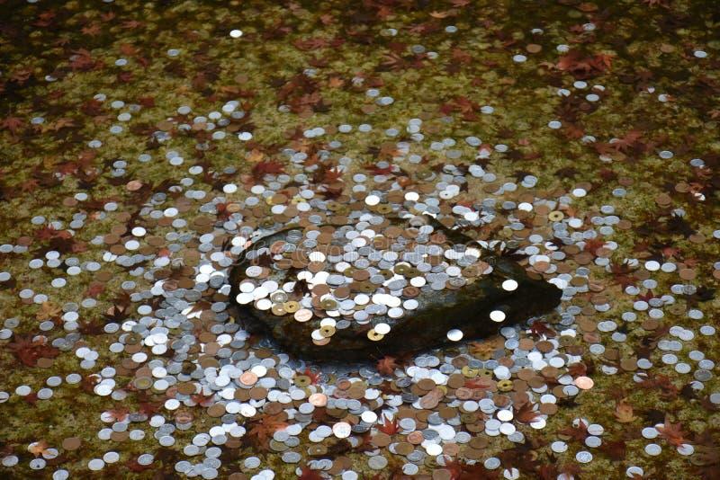 Monedas japonesas en la roca debajo del agua imagen de archivo