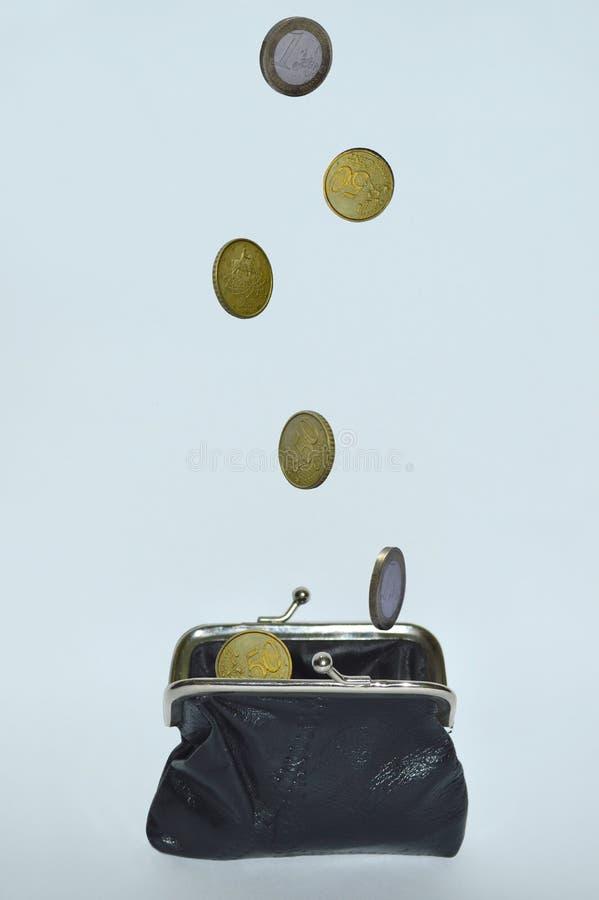 Monedas que caen en un monedero de cuero negro en un fondo blanco imagen de archivo