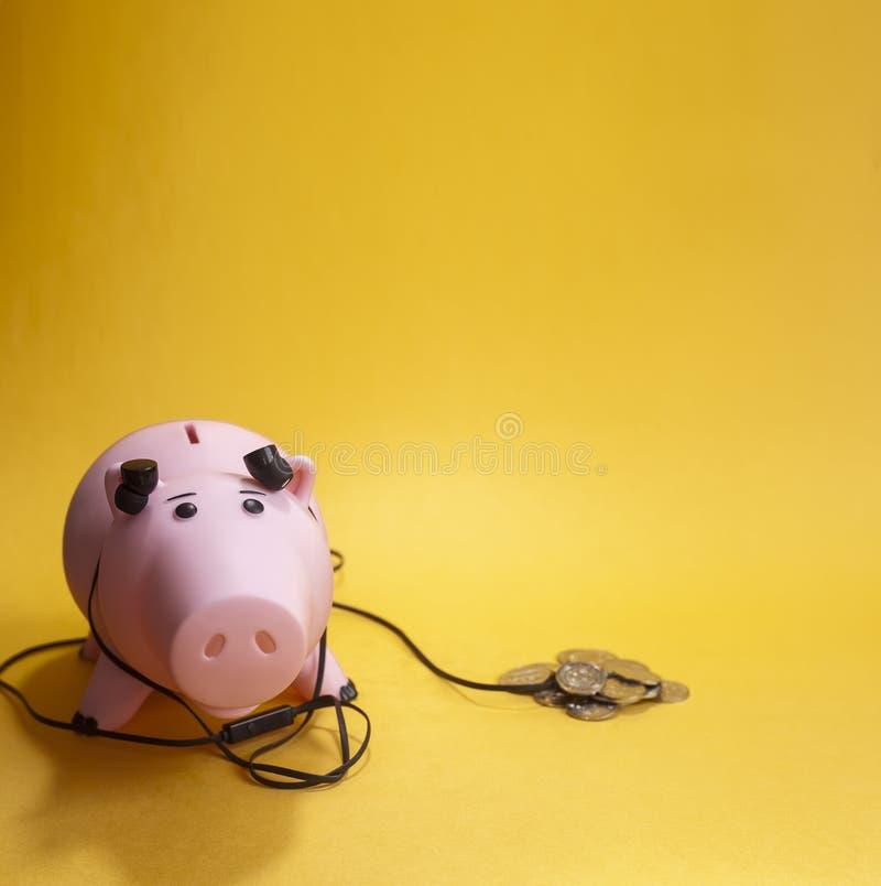 Monedas que escuchan del juguete del dinero de moneda del banco guarro de la caja con los auriculares fotografía de archivo libre de regalías