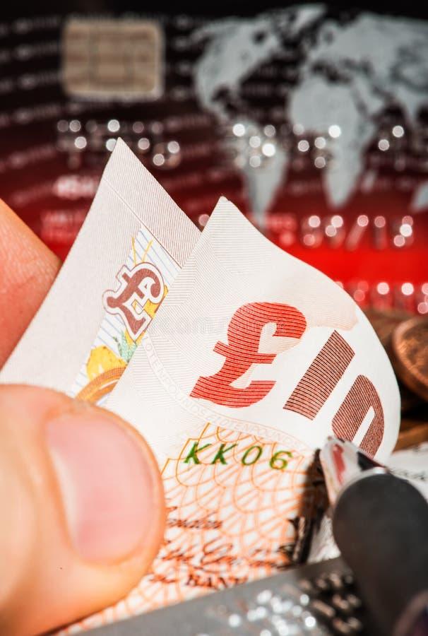 Monedas, tarjetas de crédito y libras británicas en el periódico fotos de archivo libres de regalías