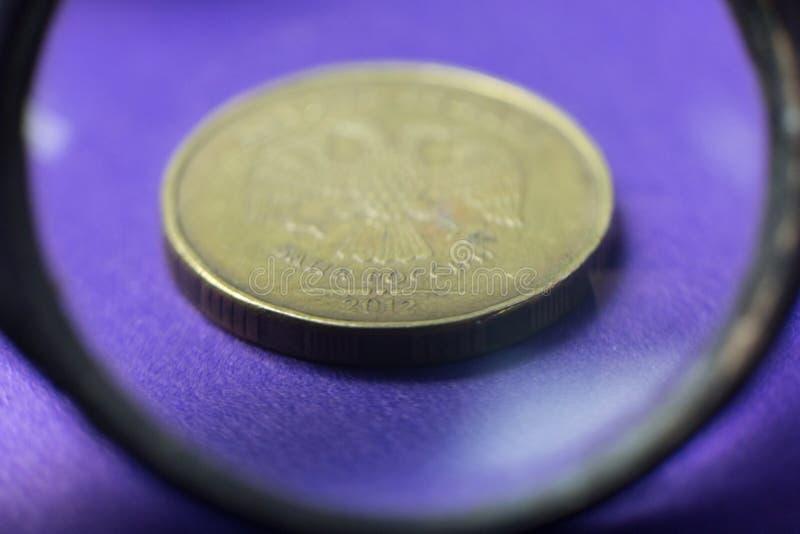 Monedas a través de una lupa imagenes de archivo